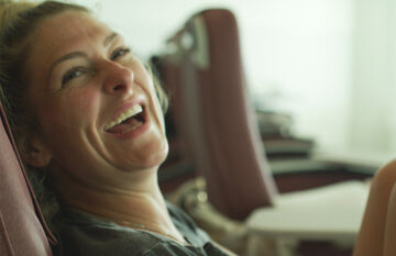 Female patient laughing while receiving IV therapy in Cancun clinic.